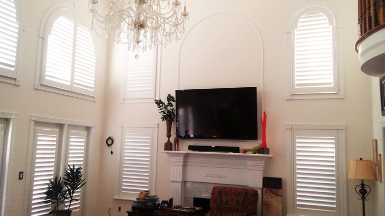 Orlando great room with mounted TV and arched windows.