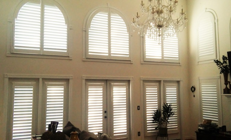 Family room in two-story Orlando house with plantation shutters on high ceiling windows.