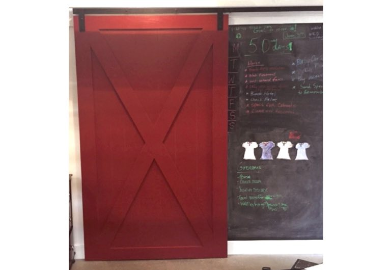 Red x-frame barn door with black track next to chalkboard