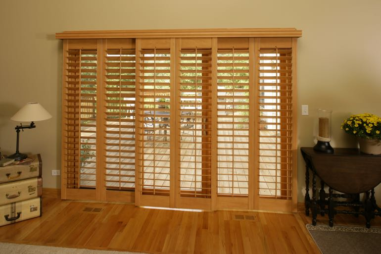 Faux wood shutters on sliding door going to outdoor porch.