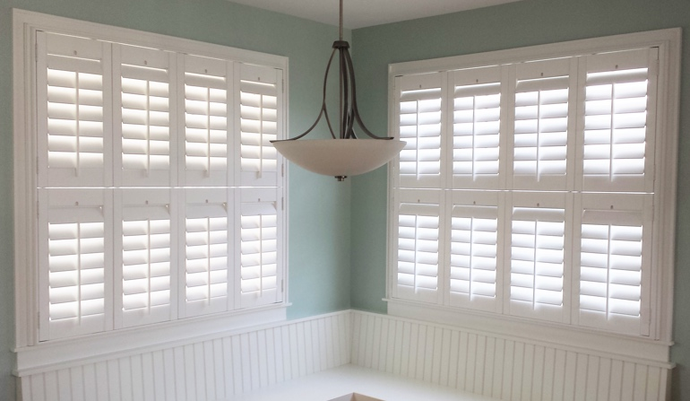 Pastel green wall in Orlando kitchen with shutters.