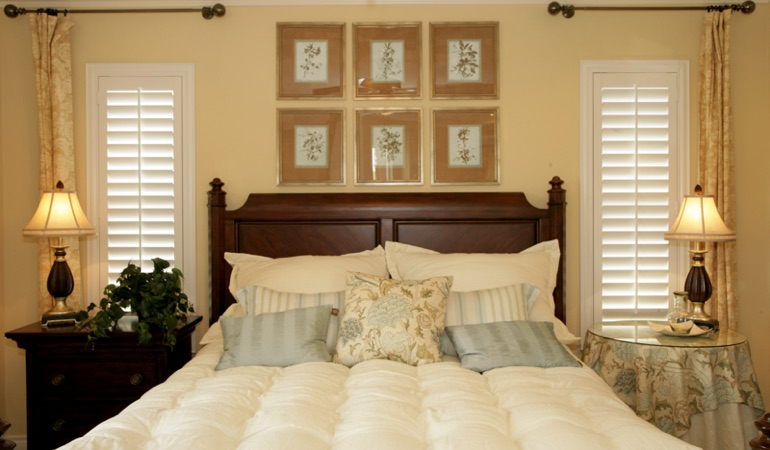Tall plantation shutters framing bed in a bedroom in Orlando