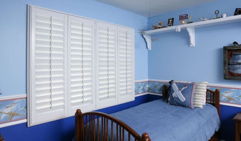 Blue kids bedroom with white plantation shutters in Orlando