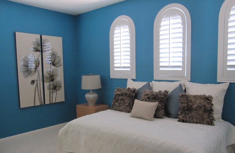 Arched plantation shutters in contemporary bedroom