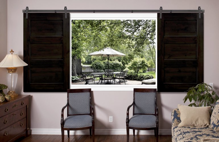 Dark brown sliding barn door shutters in family room